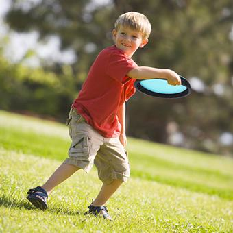A smiling young boy tosses a throwing disc or Frisbee on a sunny summer afternoon in a grassy park in Huntington Beach, Californ